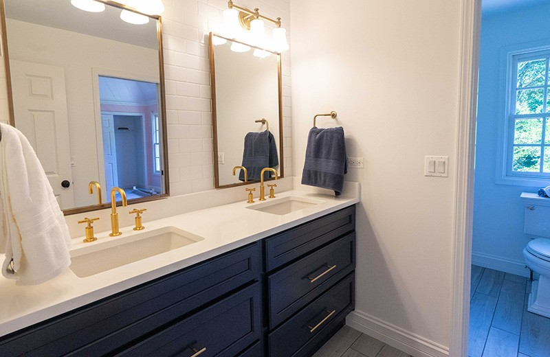 Second Floor Bathroom, navy cabinets with gold mirror