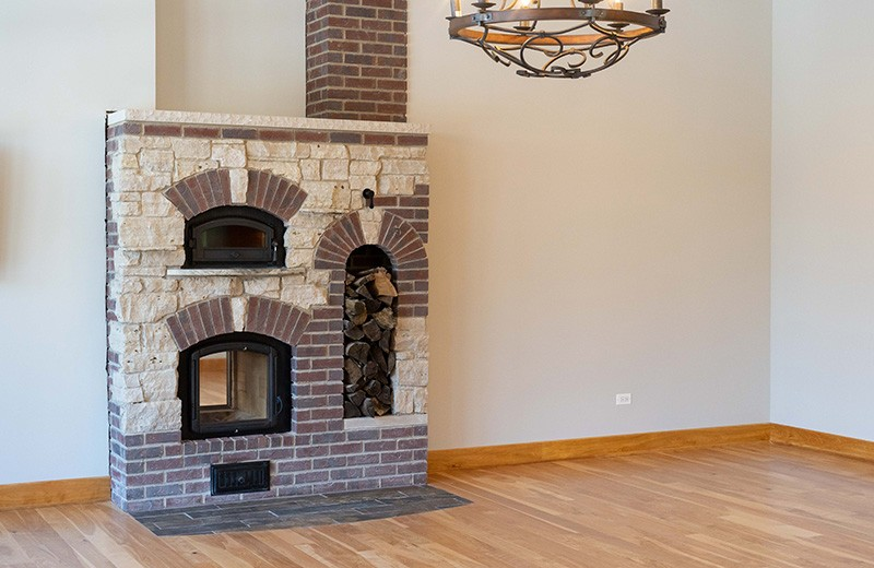 Double sided Masonry heater in living room that looks like a fireplace