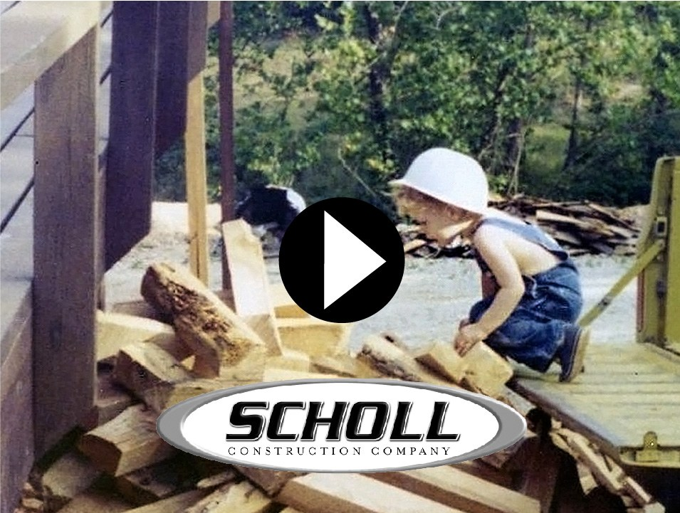 young boy in overalls and hard hat getting wood from wood pile